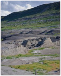 Looking West: Part of the Laramide Orogeny (mountain building episode) can be seen in the background. Vast oil deposits lie beneath these folded ridges and the black domes shown in the foreground.
